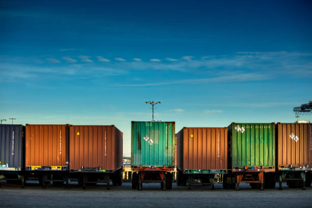 Rear view of a line of trucks loaded with differently colored shipping containers.